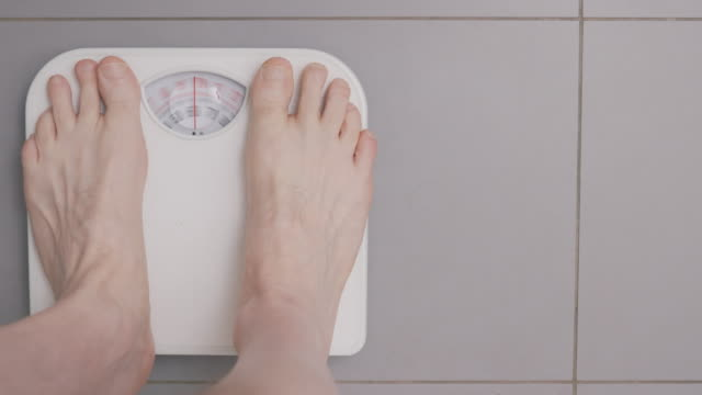 man weighing himself on  scales in luxury bathroom - 体重計点の映像素材/bロール