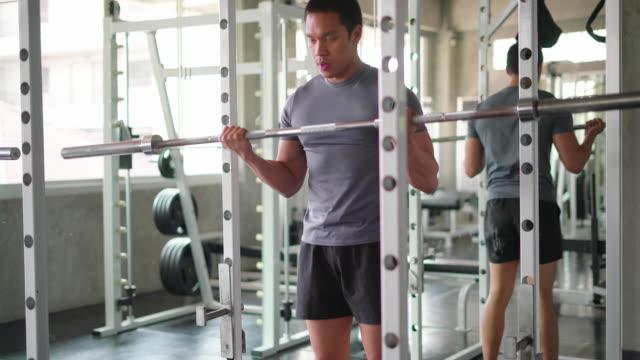 man weight lifting rods at the gym - attrezzatura per esercizio fisico video stock e b–roll