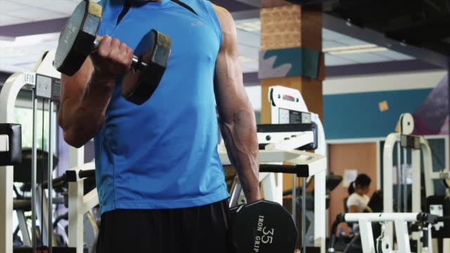 ms tu man weightlifting in gym / draper, utah, usa - ノースリーブトップ点の映像素材/bロール