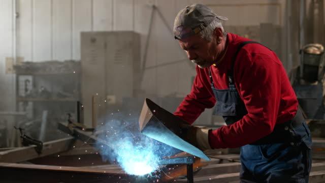 vídeos de stock, filmes e b-roll de slo mo ld man welding a metal construction - soldar