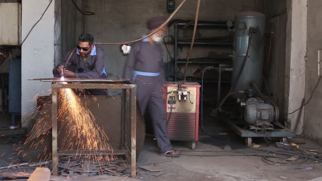 vídeos de stock, filmes e b-roll de man welding at workshop of laggar industries during customizing armored vehicles jalandhar punjab india on monday april 29 2019 - à prova de balas