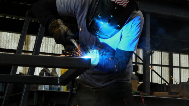 MS LA Man welding frame at bench in metal workshop