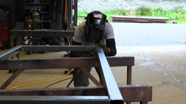 vidéos et rushes de ms man welding frame in metal shop - un seul homme d'âge moyen