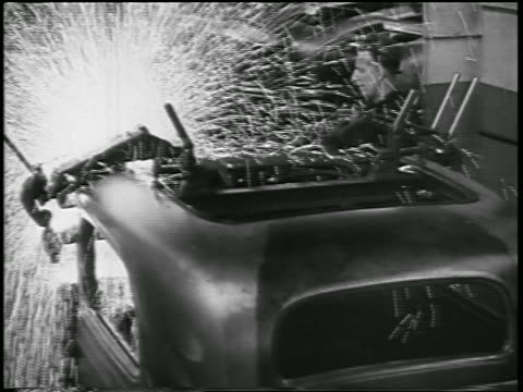 vidéos et rushes de b/w 1932 man welding front of car as sparks fly in ford car factory / industrial - ford