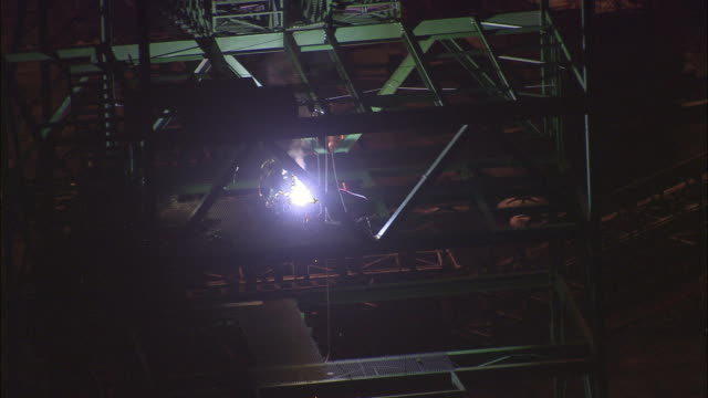 aerial ws man welding in foundry at night, rustenburg, north west, south africa - anno 2007 video stock e b–roll