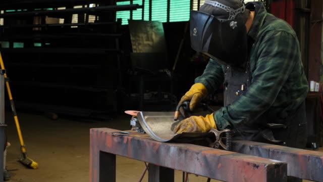 vídeos de stock, filmes e b-roll de ms man welding in metal shop - soldar