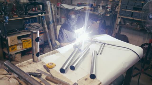 stockvideo's en b-roll-footage met man lassen in metalen workshop - argentijnse etniciteit