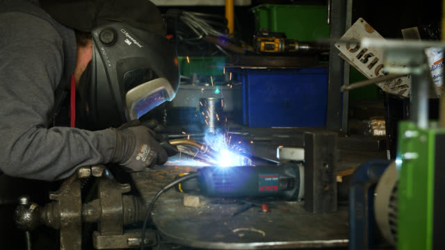 man welds metal with welding torch on workbench - welding stock videos & royalty-free footage