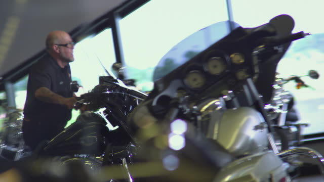 vidéos et rushes de ms man wheeling motorcycle to other side of showroom / rockford, illinois, usa - 50 54 ans