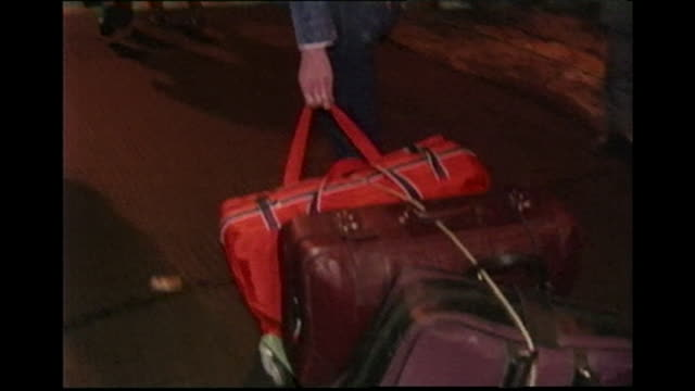 """man wheels suitcases across border between east and west berlin on the night the berlin wall fell 1989 - """"bbc news"""" stock-videos und b-roll-filmmaterial"""