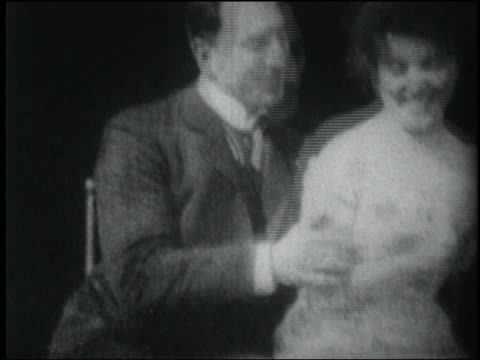 b/w 1903 man whispers to woman, kisses her on cheek, arm + lips - 1903 stock-videos und b-roll-filmmaterial