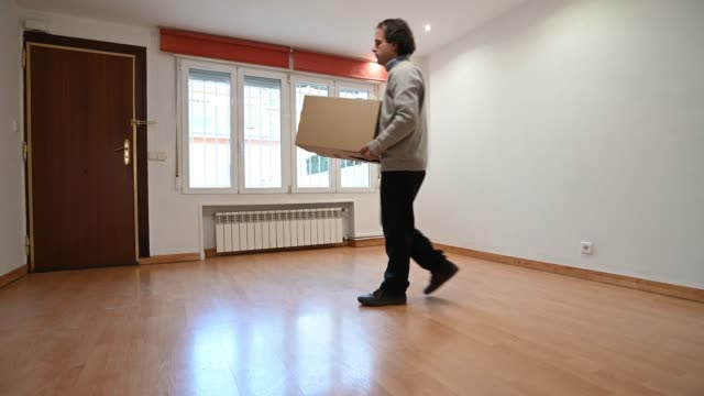 man who carries a moving box, opens the door of his house and leaves - heizung stock-videos und b-roll-filmmaterial