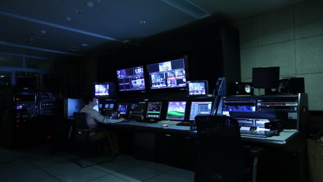 a man who control a tv broadcasting control room - sala di controllo video stock e b–roll