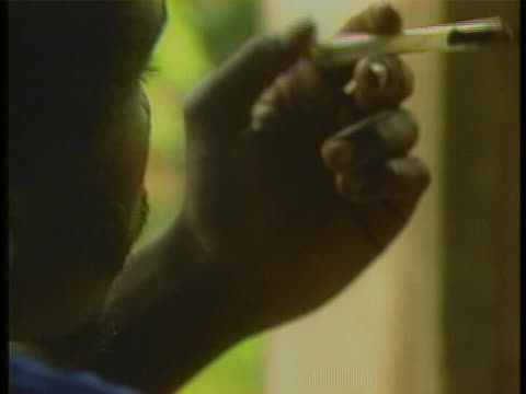 stockvideo's en b-roll-footage met man who is seen from behind smokes crack-cocaine through a glass tube. - crime or recreational drug or prison or legal trial