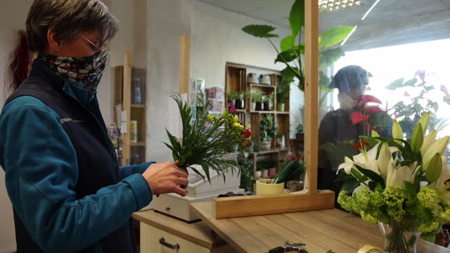 man, who said he did not mind being photographed, buys flowers at a flower shop open for the first day it reopened following a hard lockdown during... - gardening stock videos & royalty-free footage
