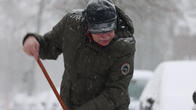 vídeos de stock e filmes b-roll de man, who said he did not mind being photographed, clears a sidewalk of snow in the district zehlendorf during a severe snow storm across germany... - pá para neve