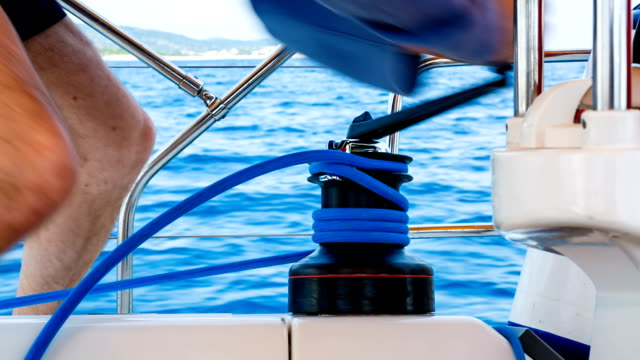 Man winding rope on winch with handle on sailboat
