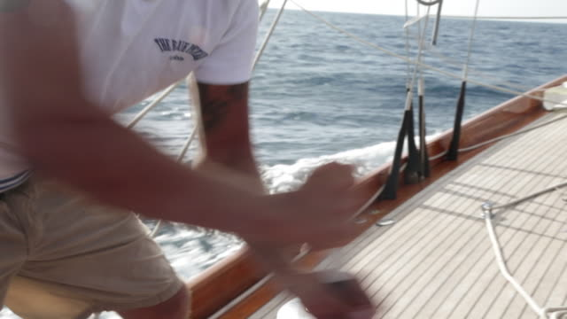 cu man winding winch on sailing yacht. - crew stock videos & royalty-free footage