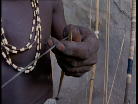 Man winds chord around tip of spear, Hadzabe tribe,