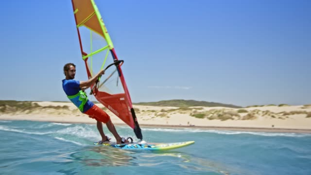 Man windsurfing and jumping into the air