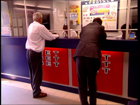 man wins half a million pounds from a 30p bet itn midlands lichfield men standing at counter of betting shop where man won half a million pounds from... - lichfield stock videos & royalty-free footage