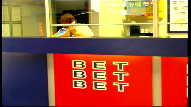 vídeos y material grabado en eventos de stock de man wins half a million pounds from a 30p bet william hill interiors itn william hill betting shop int woman on telephone as seen thru glass window... - apuestas deportivas