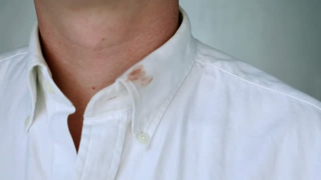 Man wiping lipstick on his collar