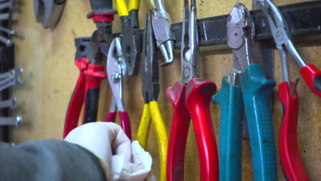man wiping pliers from a garage repair shop - rubber glove stock videos & royalty-free footage