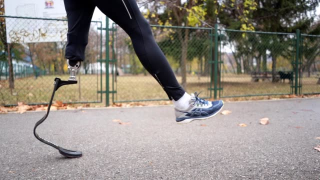man with a artificial leg warming up before running - artificial limb stock videos & royalty-free footage