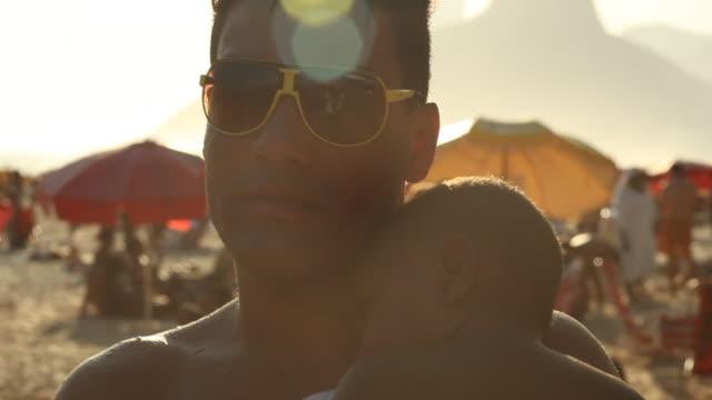 vídeos y material grabado en eventos de stock de man with a baby at the beach  - objeto fabricado