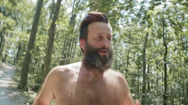 TS Man with a beard and no shirt running through the forest