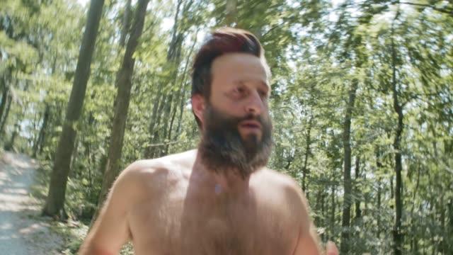 ts uomo con barba e nessuna maglia in esecuzione attraverso la foresta - a petto nudo video stock e b–roll