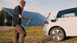 SLO MO Man with a beard plugging his car for charging it from solar energy at home