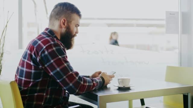 vídeos y material grabado en eventos de stock de ds de hombre con barba con un teléfono inteligente en el café - camisa a cuadros