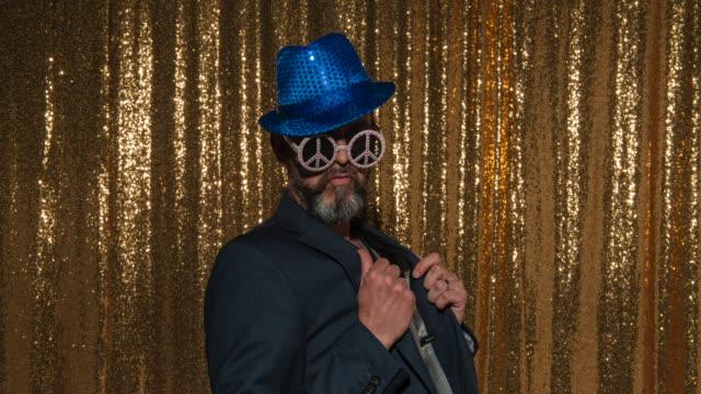 パーティーでフォトブースでポーズをとりながら、青いキラキラ帽子とネクタイを着用したひげを生やした男 - 中年の男性一人点の映像素材/bロール