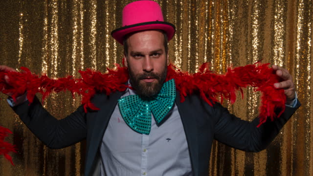 man with a beard wearing party props and taking fun photos in the photo booth - medium shot stock videos & royalty-free footage