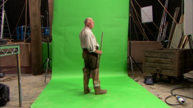 vídeos de stock e filmes b-roll de a man with a bucket and a broom appears confused as he stands in front of a green screen in a warehouse. - porteiro