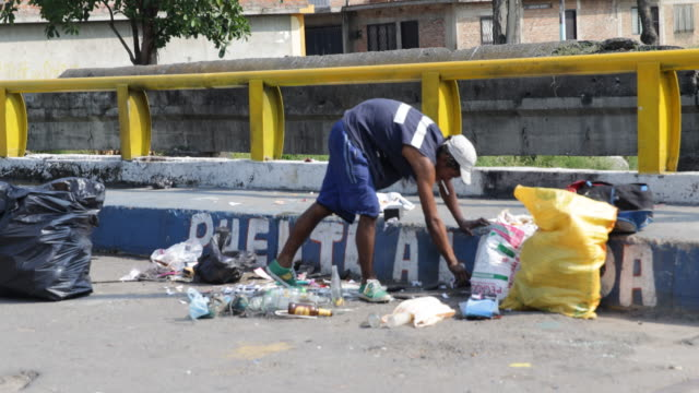 a man with a cigarette in his mouth rummaging in trash on a bridge known as a selling point for drugs in el vertel a neighborhood with high... - america del sud video stock e b–roll