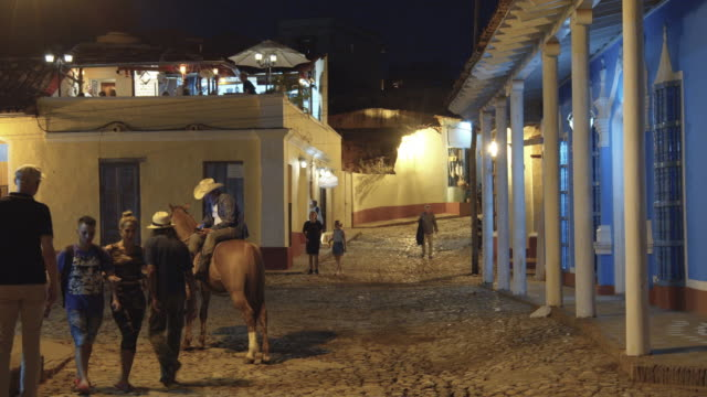 man with a cowboy hat sitting on the back of his horse at a street corner in trinidad, cuba, filmed in the evening - village stock videos & royalty-free footage