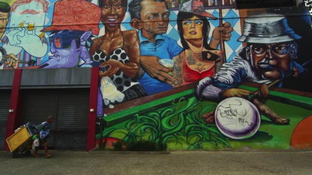 rio de janeiro-june 23: man with a crate passes graffiti wall on jun 23, 2013 in rio, brazil - brasilien stock-videos und b-roll-filmmaterial