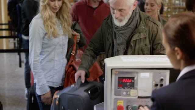 vídeos de stock e filmes b-roll de man with a grey beard placing his bag on the conveyor belt at the check in desk - bagagem