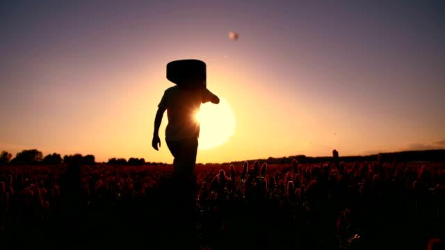 SLO MO Man with a guitar walking at sunset
