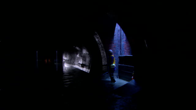 a man with a headlamp walks through a dark sewer. - walking in water stock videos & royalty-free footage