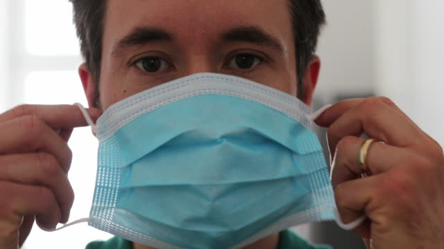 man with a medical mask in self quarantine at home - applying stock videos & royalty-free footage