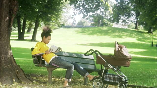 stockvideo's en b-roll-footage met man with a pram in a park, sweden. - haar naar achteren