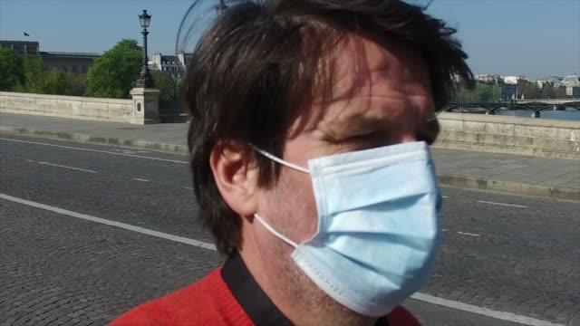 man with a protective mask walks on the new bridge without traffic and without people during the coronavirus epidemic on april 8 in paris, france.... - ポンヌフ点の映像素材/bロール