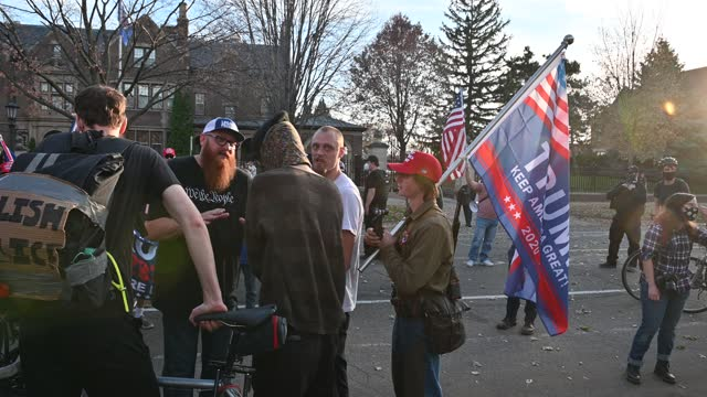man with a rifle holding a trump flag walks around as supporters of president donald trump gather outside the governor's mansion on november 7, 2020... - waffe stock-videos und b-roll-filmmaterial
