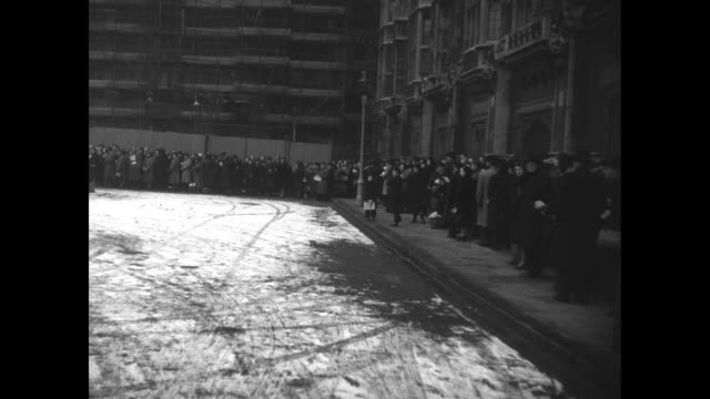ws pan man with a shovel in a parking lot with light snow and pan to long line of people / pan women with younger man with elaborate rope tied around... - 1952 bildbanksvideor och videomaterial från bakom kulisserna