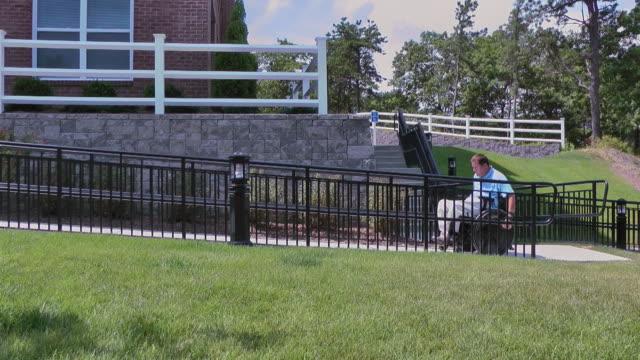 vídeos de stock e filmes b-roll de a man with a spinal cord injury struggles to roll his wheelchair up a ramp. - paralisia