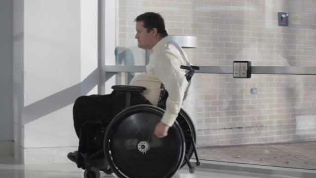 vídeos de stock e filmes b-roll de a man with a spinal cord injury uses an automatic door to enter a building. - paralisia